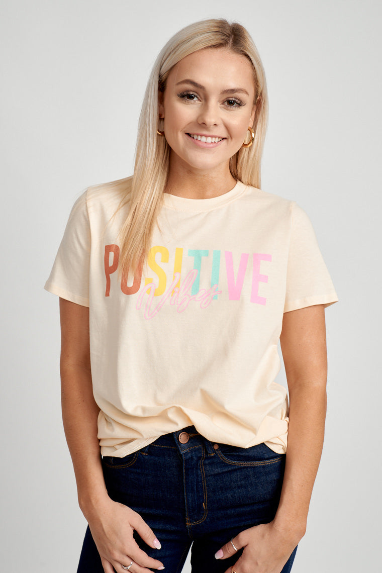 "This natural yellow t-shirt has short sleeves that attach to a u-neckline on a relaxed bodice. The word ""Positive"" is written across in colors while ""vibes"" is outlined in pink."