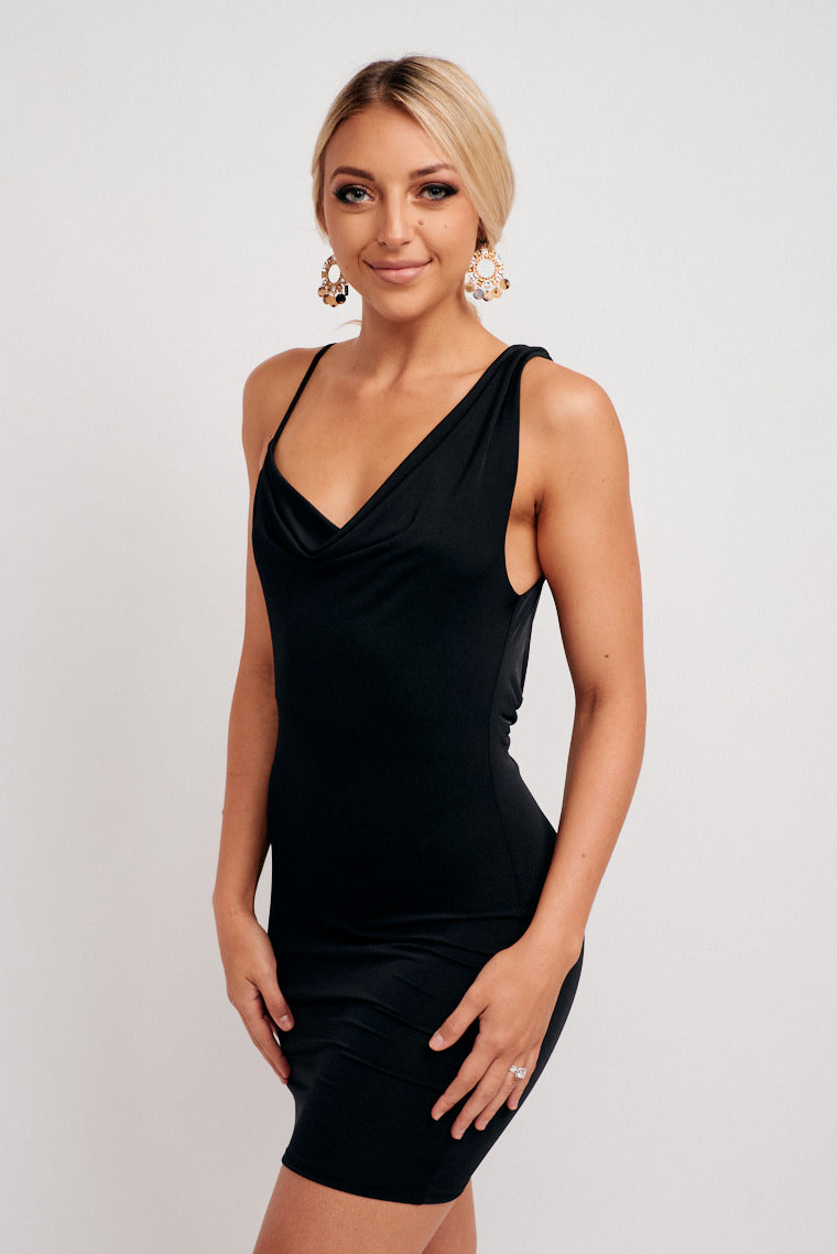 A thin strap attaches to one end of a v-neckline while a thick strap attaches to the other side and goes into a fitted bodice silhouette and leads down to a fitted mini skirt.