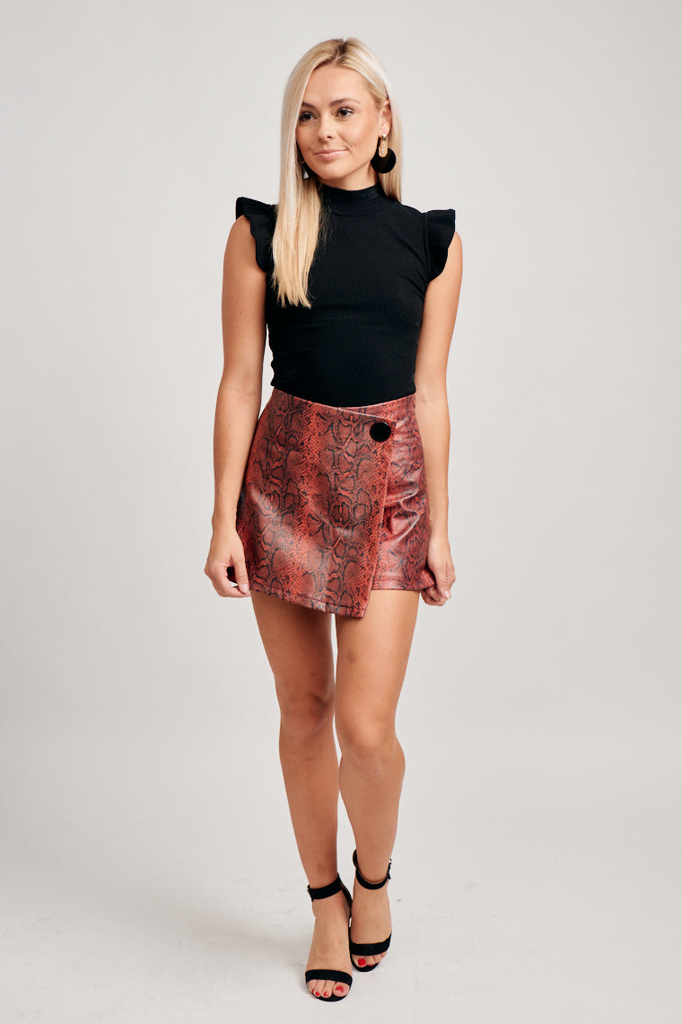 This skort has a fitted waistband that leads to a skirt panel with a button detail lays atop of fitted shorts. This skort features a zipper on the back.