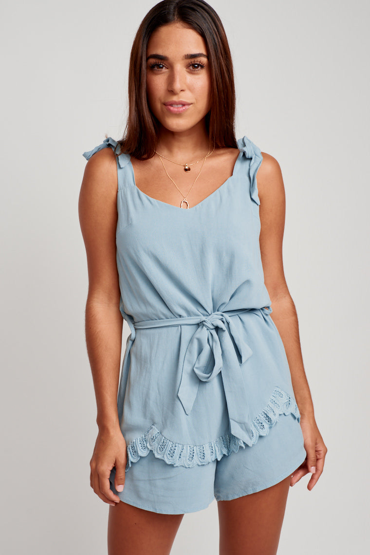 This romper has medium tie straps that meet a soft v-neckline that hold an oversized silhouette bodice with a crochet scallop hem detail leading to the shorts.