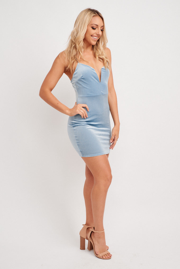 This mini dress has thin straps attach to a deep v-neckline that leads to a fitted and darted bodice with a fitted waist and leads to a hip-hugging mini skirt.