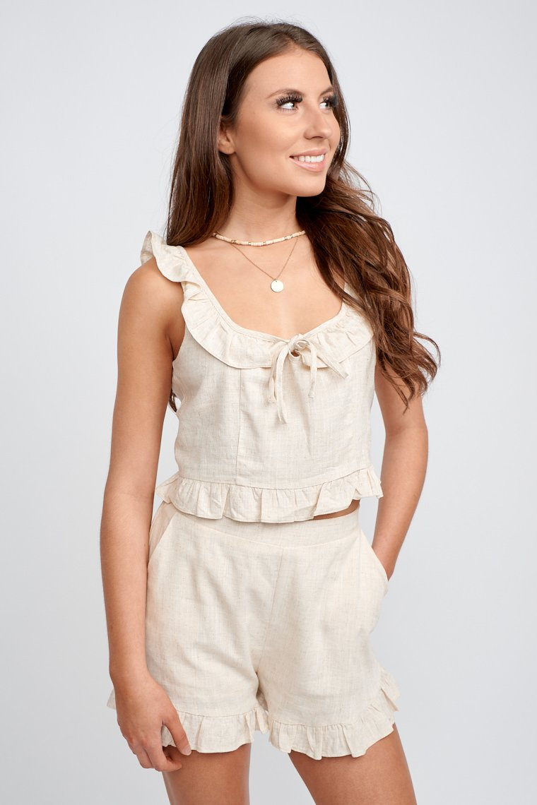 This lightweight top has medium straps that attach to a u-neckline with a fluttery ruffle hem atop it and a tie at the center, relaxed fit cropped bodice with a ruffle hem.