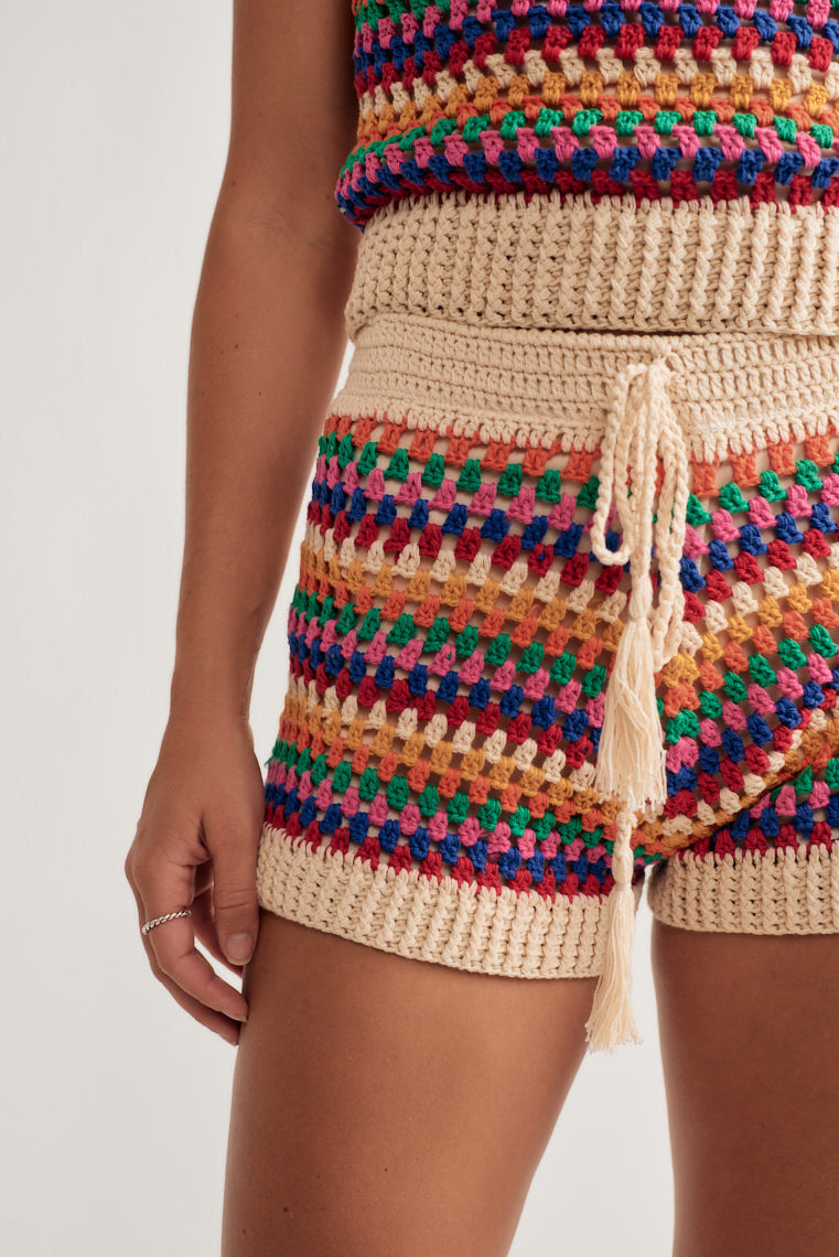 Rainbow crochet knit forms this cute tank top with thin, knit straps on a v-neckline and relaxed silhouette.