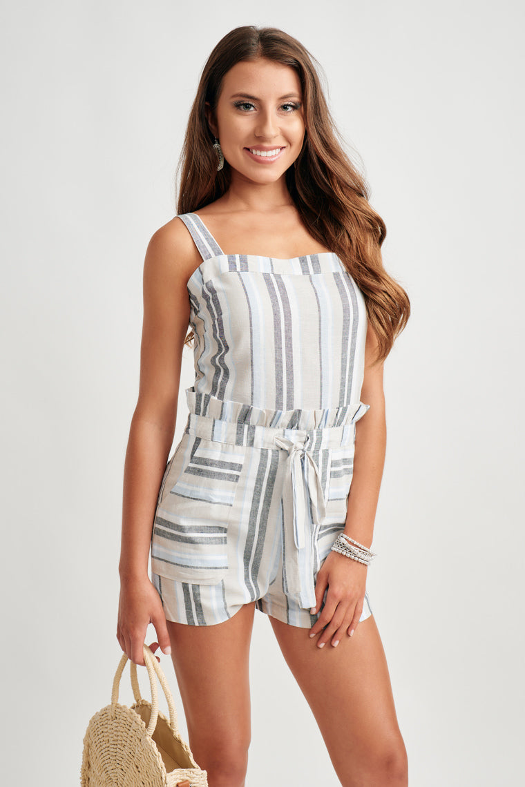 This lightweight, striped romper offers thick straps to the straight neckline, paper bag style waistline atop relaxed shorts with front and back pockets.