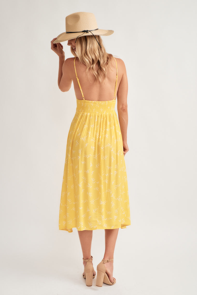 adjustable skinny straps on a triangle, ascending point bodice with a banded waist carries into a flowy, A-line midi hem.