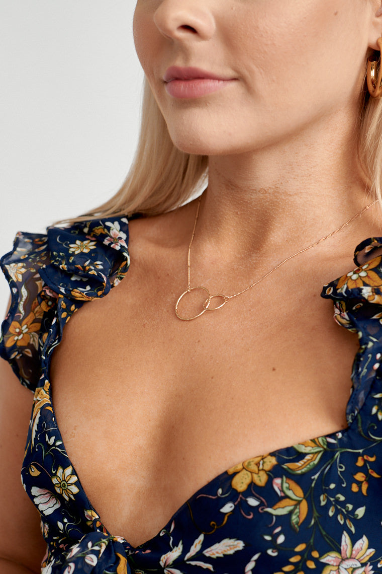This necklace has a thin chain that reaches to small and large interlocking circles that drape across the collarbone. It's perfect on its own or to stack with other necklaces!