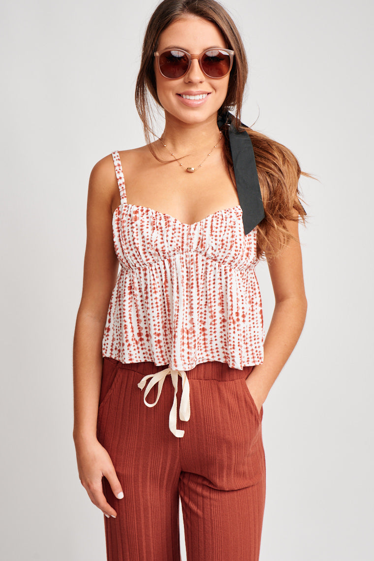 This cropped tank has thin adjustable straps that attach to a gentle v-neckline and shirred bust panel. It flows into a baby doll style cropped bodice.