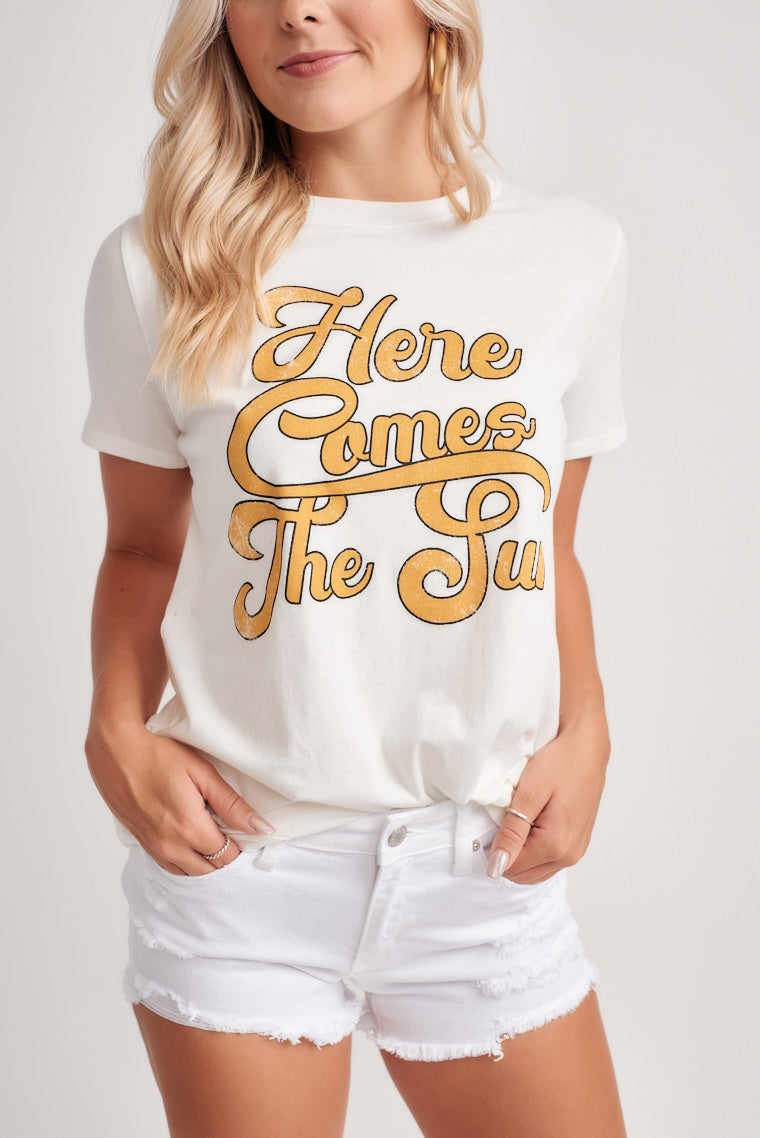 "This ultra-comfortable graphic tee has the saying ""here comes the sun"" in fun illustrative writing on top a crew neckline, short sleeves, and a relaxed fit."