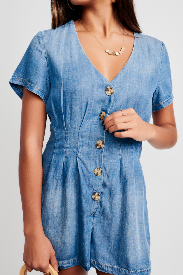 Medium wash romper has short sleeves, a v-neckline that flows into a relaxed button-down bodice which is darted across the waist and has oversized shorts.