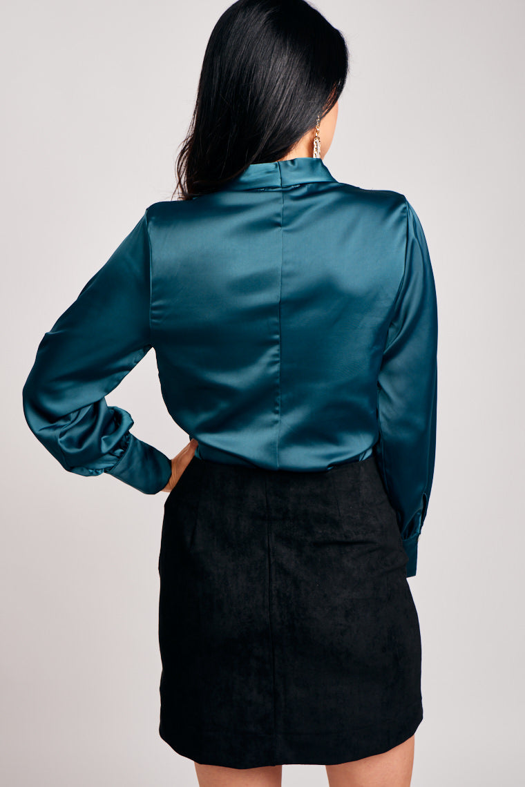 Long banded cuff sleeves attach to a surplice neckline and lead to a relaxed and oversized bodice silhouette. This blouse features a zipper at the side.