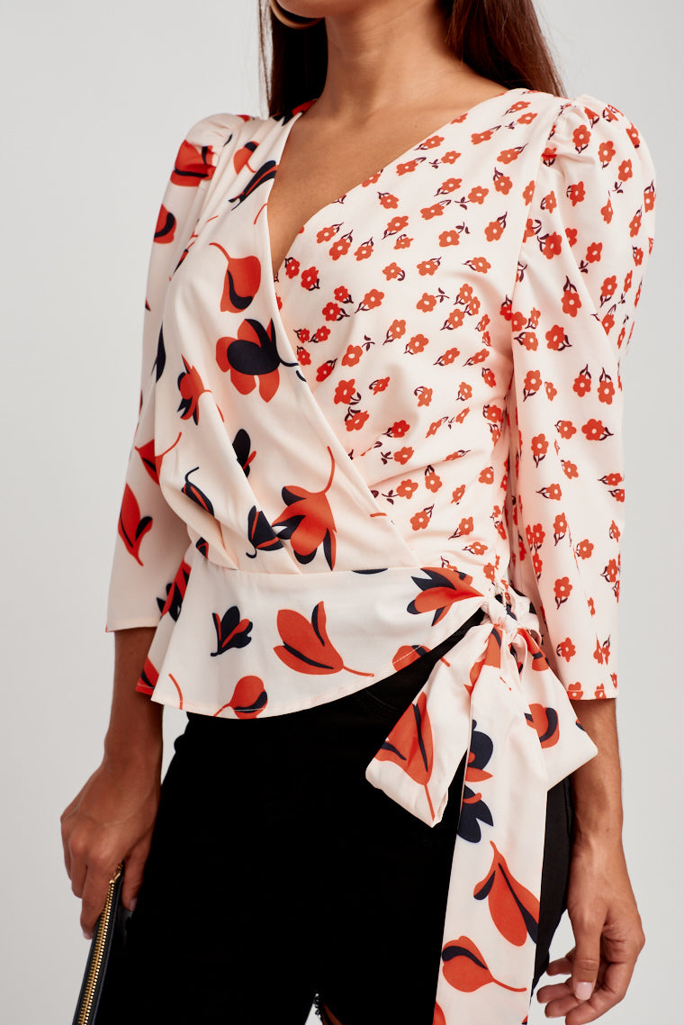 This whimsical two patterned fabric blouse has puff medium sleeves that connect to a surplice neckline with a fabric tie that ties at the side.