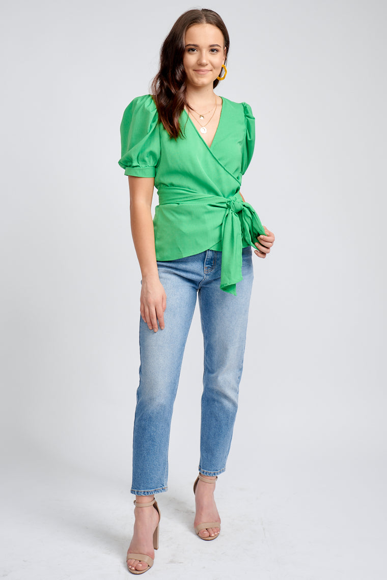 Mid-length banded puff sleeves attach to a surplice neckline on a relaxed fit bodice silhouette, extended fabric ties that circle the waist and tie at the side or front.