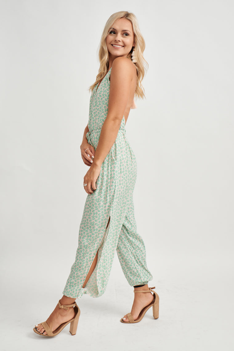 This unique green printed jumpsuit has a faint, light pink shade background, a halter tying neckline supports bodice with a modesty snap and offering an open back.