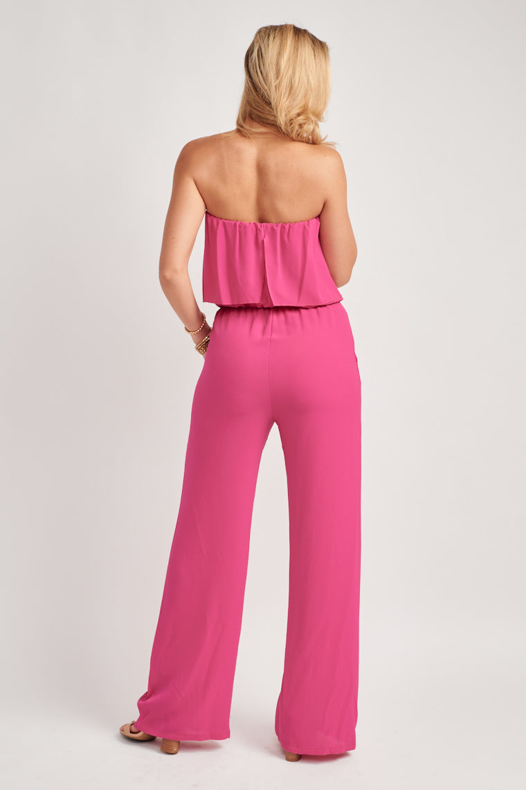 This hot pink jumpsuit will really make a statement. The strapless neckline moves to a flounced bodice with an elasticized waistline and flowy wide pant leg.