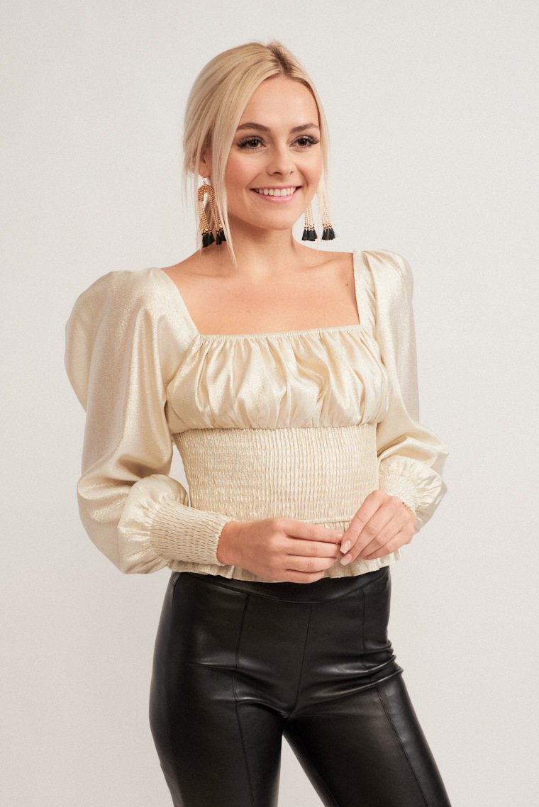 This darling top has a shiny gold-threaded fabric with mid-length puff sleeves that attach to a square neckline and lead to a tiered and smocked bodice.
