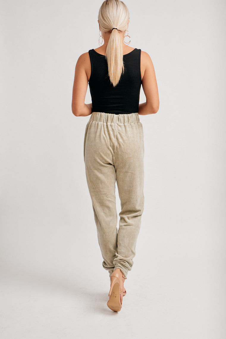These comfy sweats have an elastic waistband with an adjustable drawstring tie that leads to square pockets and relaxed fit pant legs with banded cuffs at the ankles.