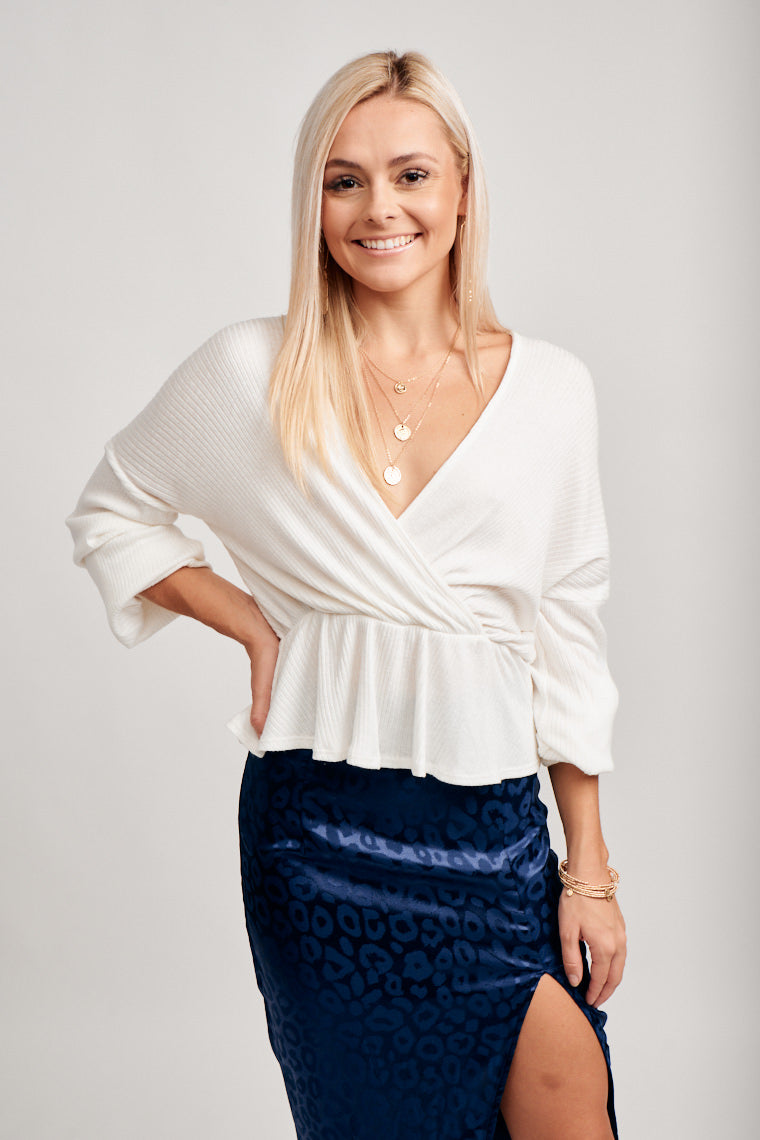 Long sleeves attached to a surplice neckline goes into an oversized and relaxed fit bodice that leads to an elastic waistband with a peplum-style hem.