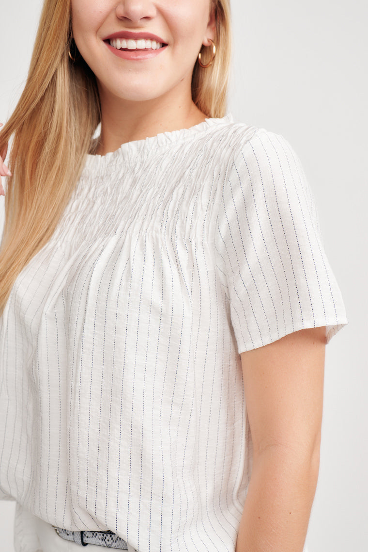 This lightweight striped blouse features a ruffled neckline with a drawstring tie in the back and a gentle smocked detail at the neckline that flows into the bodice.