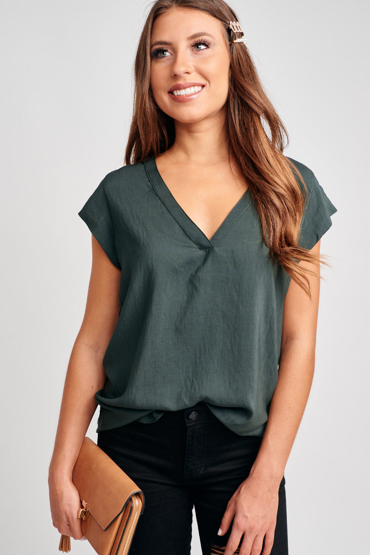 This short-sleeved blouse has a banded v-neckline that goes into a comfortable and relaxed bodice silhouette. Pair with high-rise distressed boyfriend jeans.