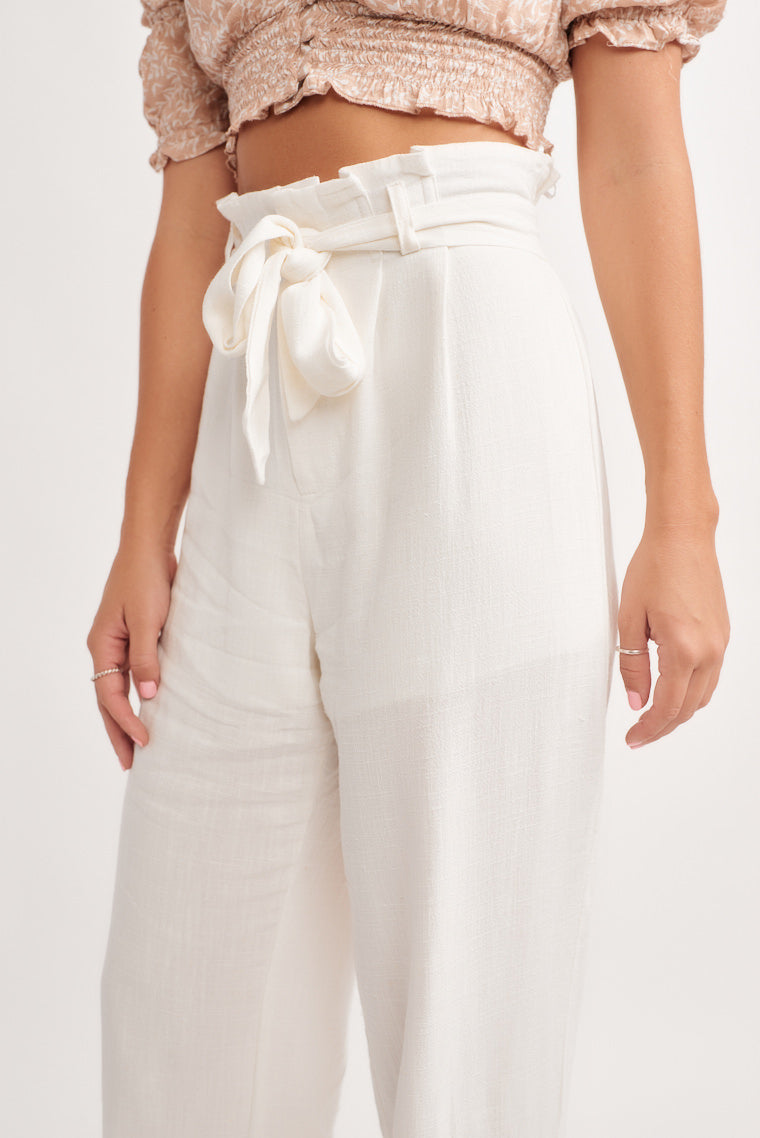 These lightweight white paper bag style pants offer a high rise fit and a tie sash around the waist. These pants feature a front button and zipper closure.