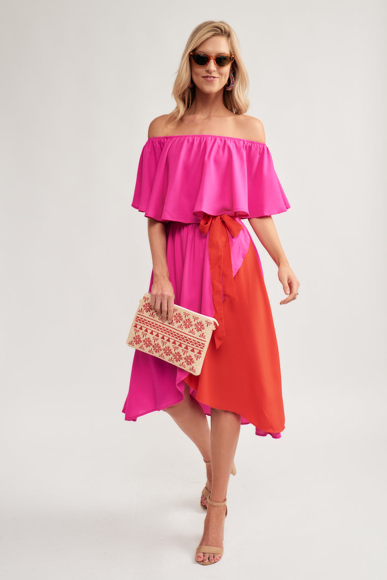 This hot pink, off the shoulder midi dress, features an elasticized neckline paired with a flounced bodice atop a cinched waistline that moves into a color-block pink and red surplice style high-low skirt.