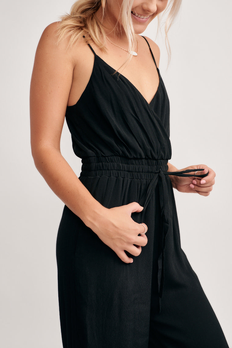 This black jumpsuit offers a surplice neckline that ends at the waistband and flows into pants detailed with a horizontal white stripe across the bottom.