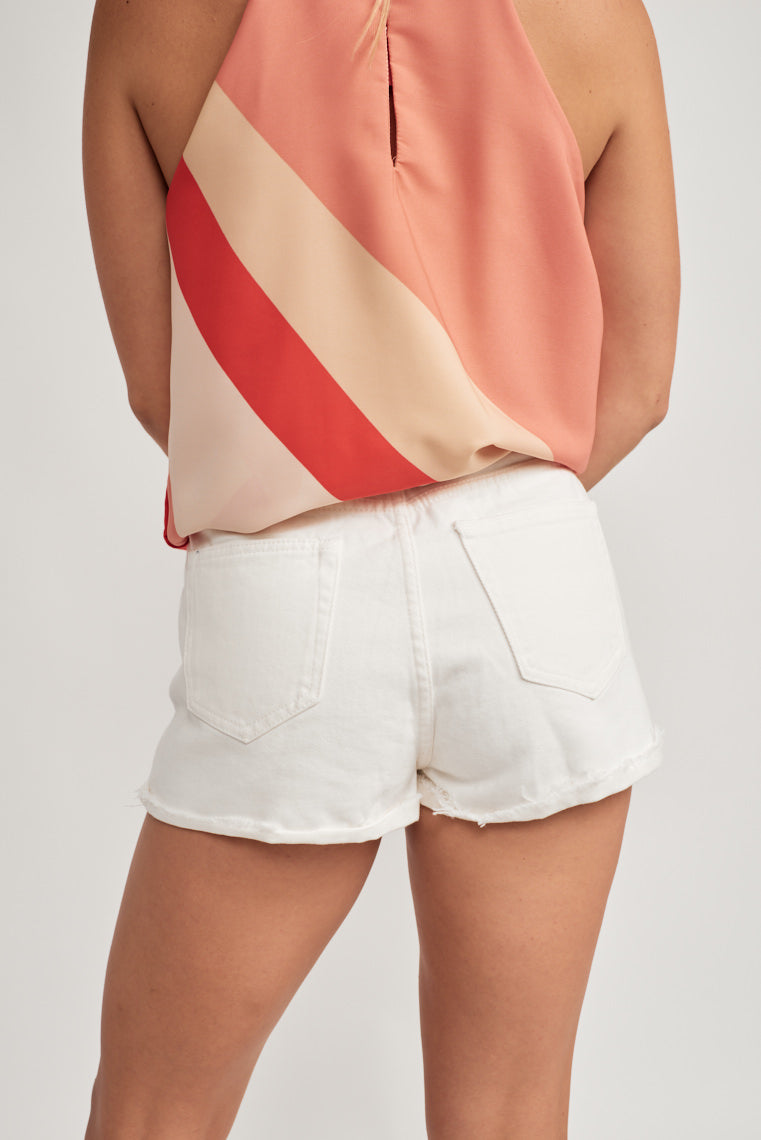 These white denim shorts feature a mid-rise waistline with belt loops, classic five cut pocket and lightly distressed with a cuff, raw edge hem