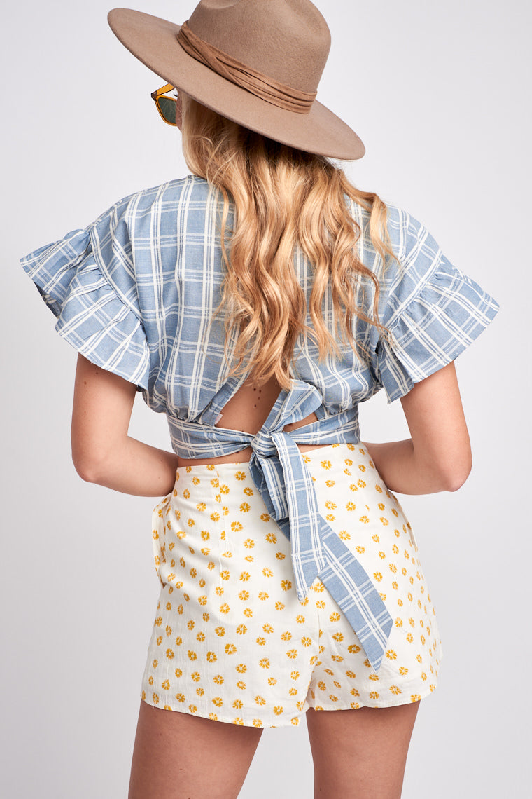 Small yellow flowers cover the fabric of these cute shorts. It has a fitted waistband and leads down to lightweight and hip-hugging shorts with darts down the back.