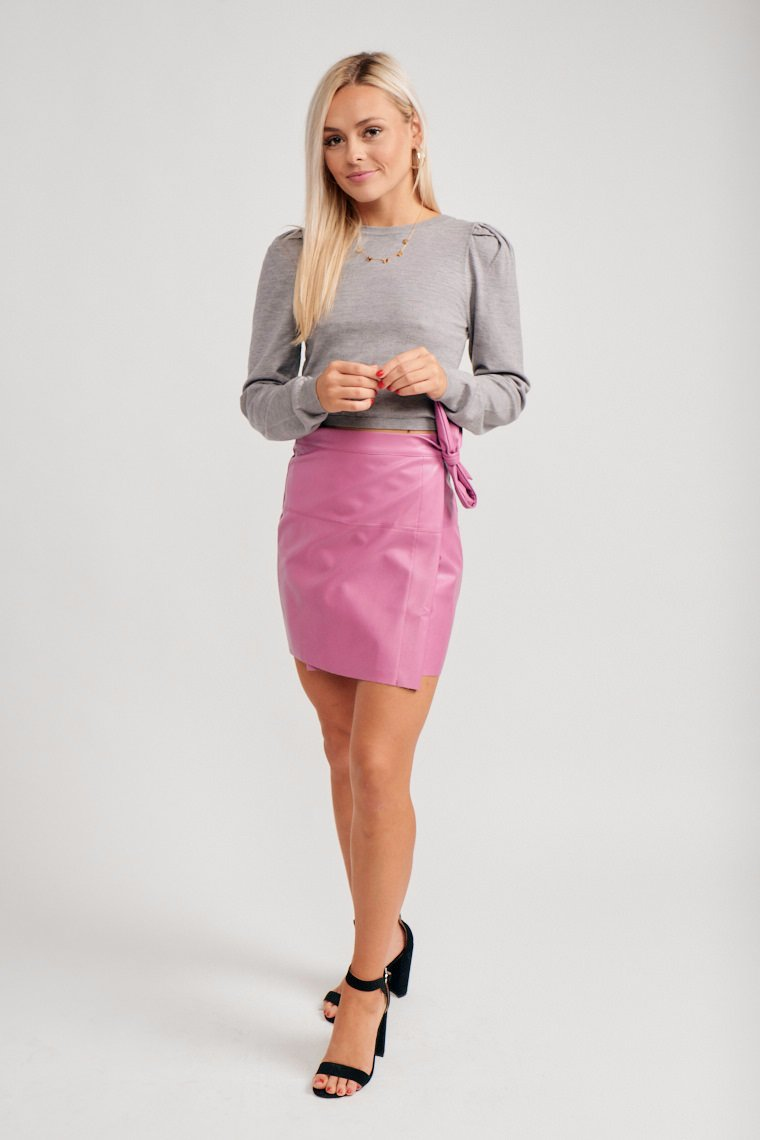 This bright fuschia skirt has a fitted waistband that leads to an a-line silhouette and has a skirt panel that ties at the side atop it.