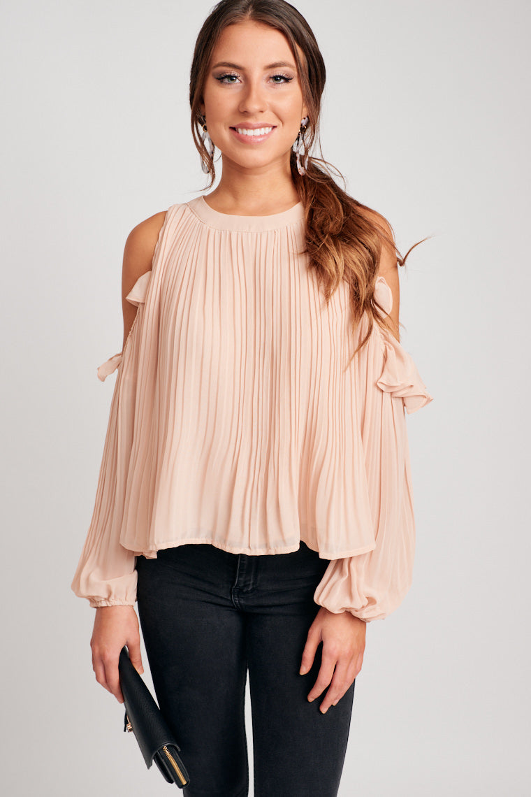 This long-sleeve elastic cuffed cold shoulder top has ruffle detailing, attaches to a high banded u-neckline and leads to a flowy and relaxed pleated bodice.
