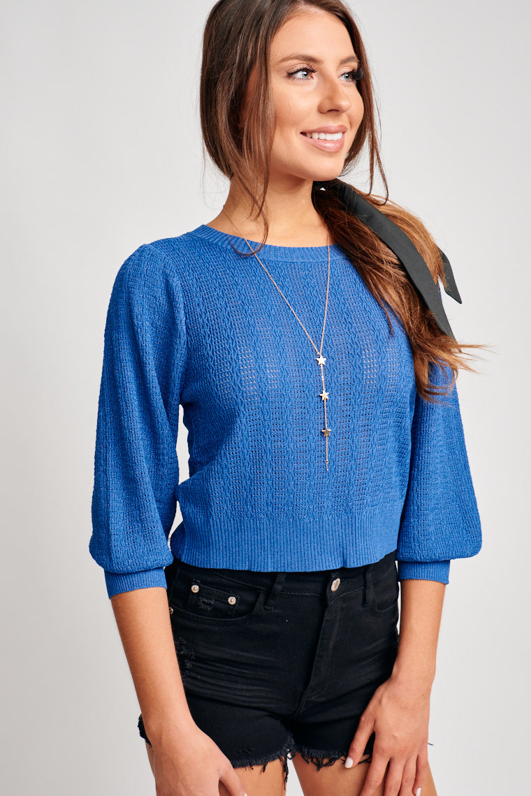 Medium length sleeves that are slightly puffed are attached to a high u-neckline and flow down to a relaxed knit and cropped bodice.