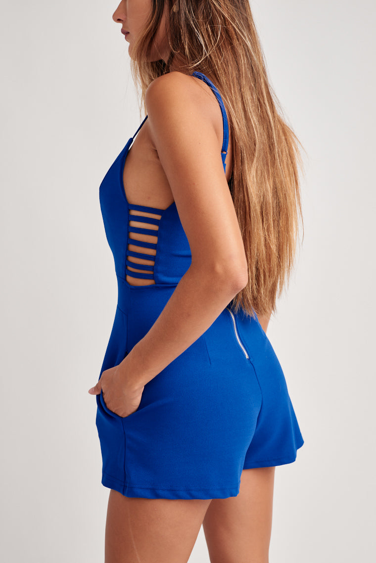 Blue romper supported by adjustable skinny straps on a v-neckline that carries into a fitted bodice with side latter cutouts and semi-fitted shorts.