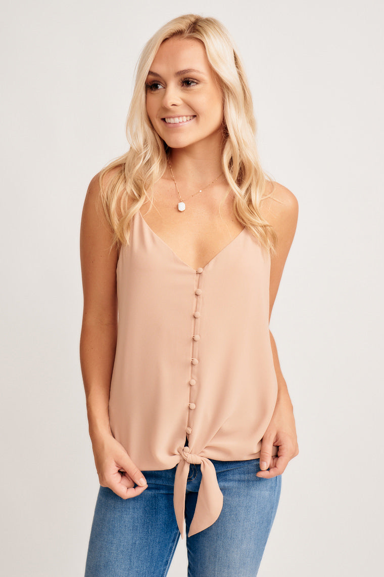 This lightweight tank top has v-neckline, adjustable skinny straps that attach onto a relaxed, button-down bodice with a tie front hem. Style with jeans!
