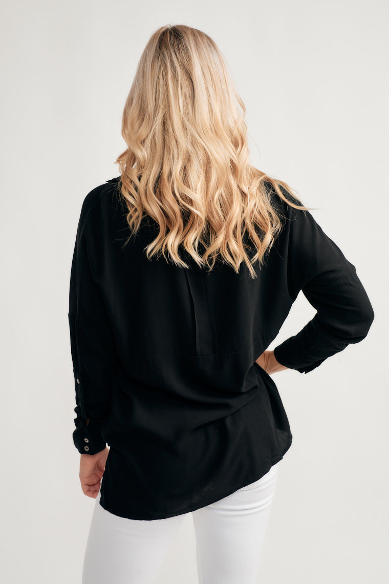 This black lightweight blouse features a three, button-up bodice with a collared-neckline, two front pockets on a relaxed silhouette and long sleeves, rolled to a button.