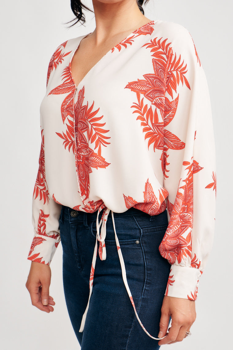 This long sleeve blouse has a red paisley floral print which covers the surplice neckline and flowy bodice. This blouse features a drawstring tie at the waist.