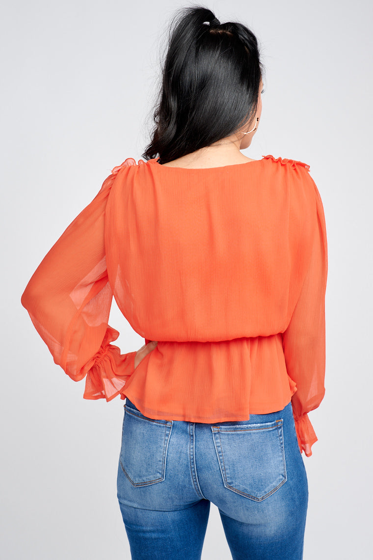 Long ruffle sleeves attach to a surplice neckline with ruffle details at the shoulder and lead to a comfortable bodice silhouette to an elastic waistband with a peplum-style hem