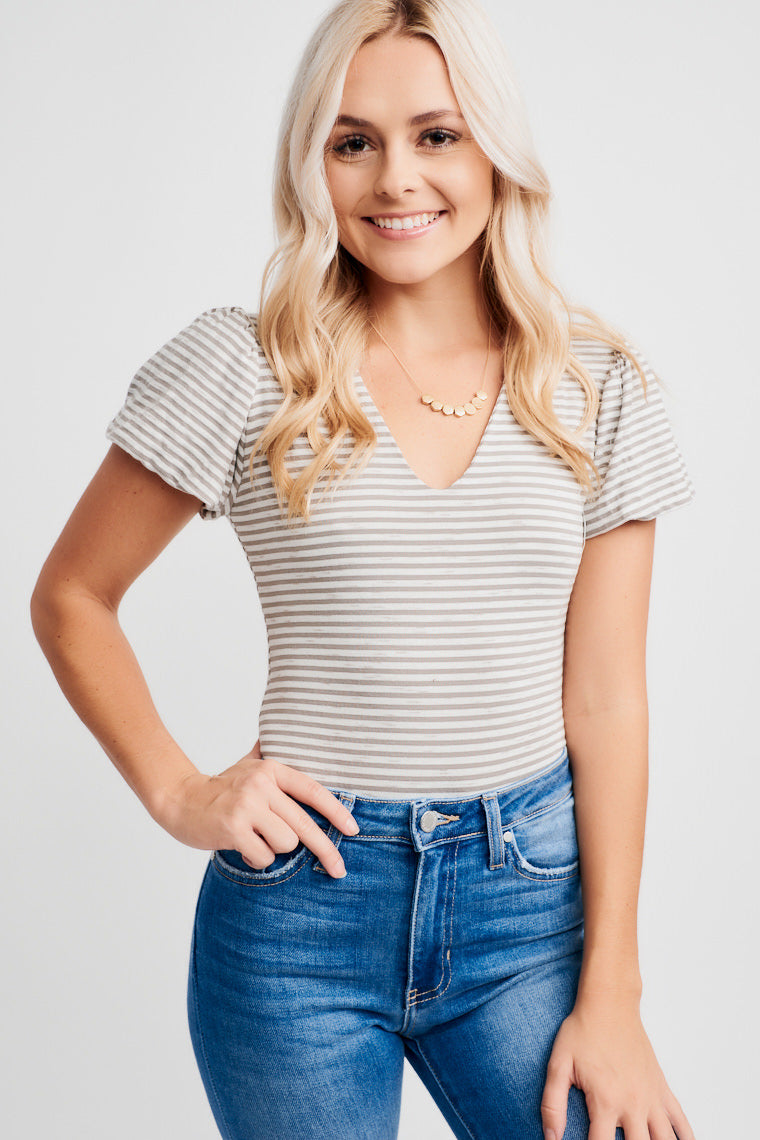 This striped bodysuit offers puffed sleeves that attach onto a v-neckline and fitted bodice. This bodysuit features metal closures in the inseam.