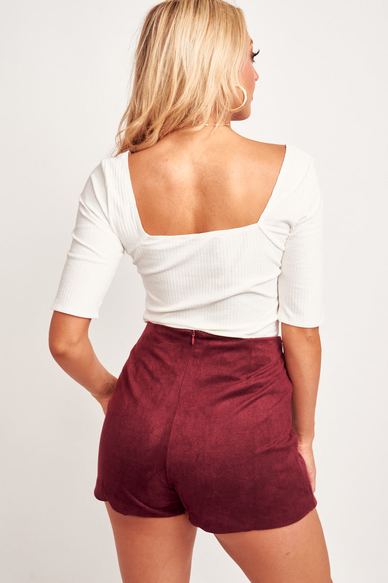 This comfortable white top has mid-length sleeves that attach to the square neckline with a fitted knit bodice. Pair with high-rise jeans and sandals.