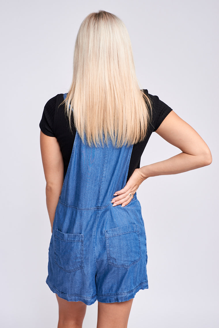 Thin tie straps go through grommets on a classic overall bodice with a straight neckline and front chest pocket, down into oversized and comfortable shorts.