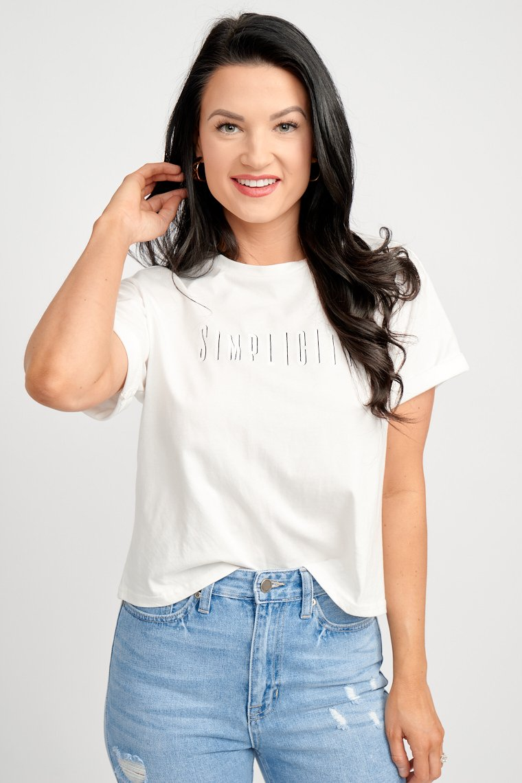 "Short sleeves that attach to a relaxed and cropped bodice silhouette. The word ""Simplicity"" is in white and black outlined text across the chest."