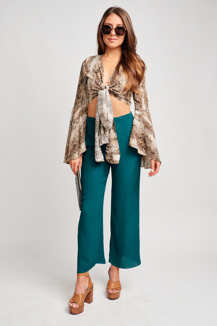 This fun snake printed top has long bell-sleeved arms that attach to a deep v-neckline and leads to a tie-front hem that could be wrapped around your waist.