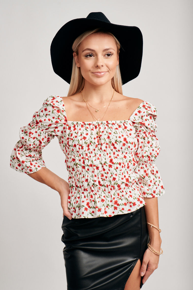 This red floral printed top has mid-length puff sleeves that attach to a square neckline that leads to a comfortable elastic-tiered bodice.