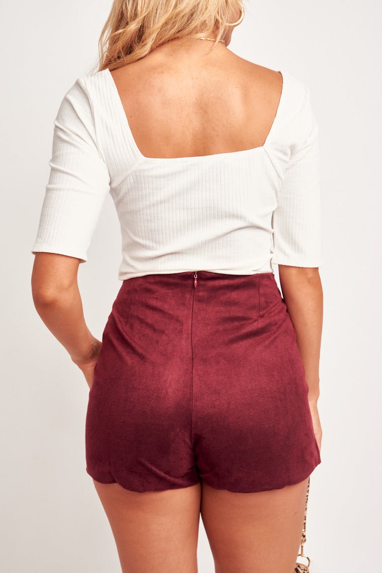 Three buttons detail the skirt panel leading to an asymmetric slit atop fitted shorts. This skort features a zipper and hook and eye closure on the back to secure.