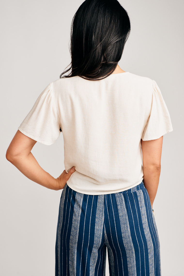It's easy to pair this with a variety of bottoms. This short sleeve top has a deep v-neckline that goes into a relaxed button-down bodice with tie-front hem.