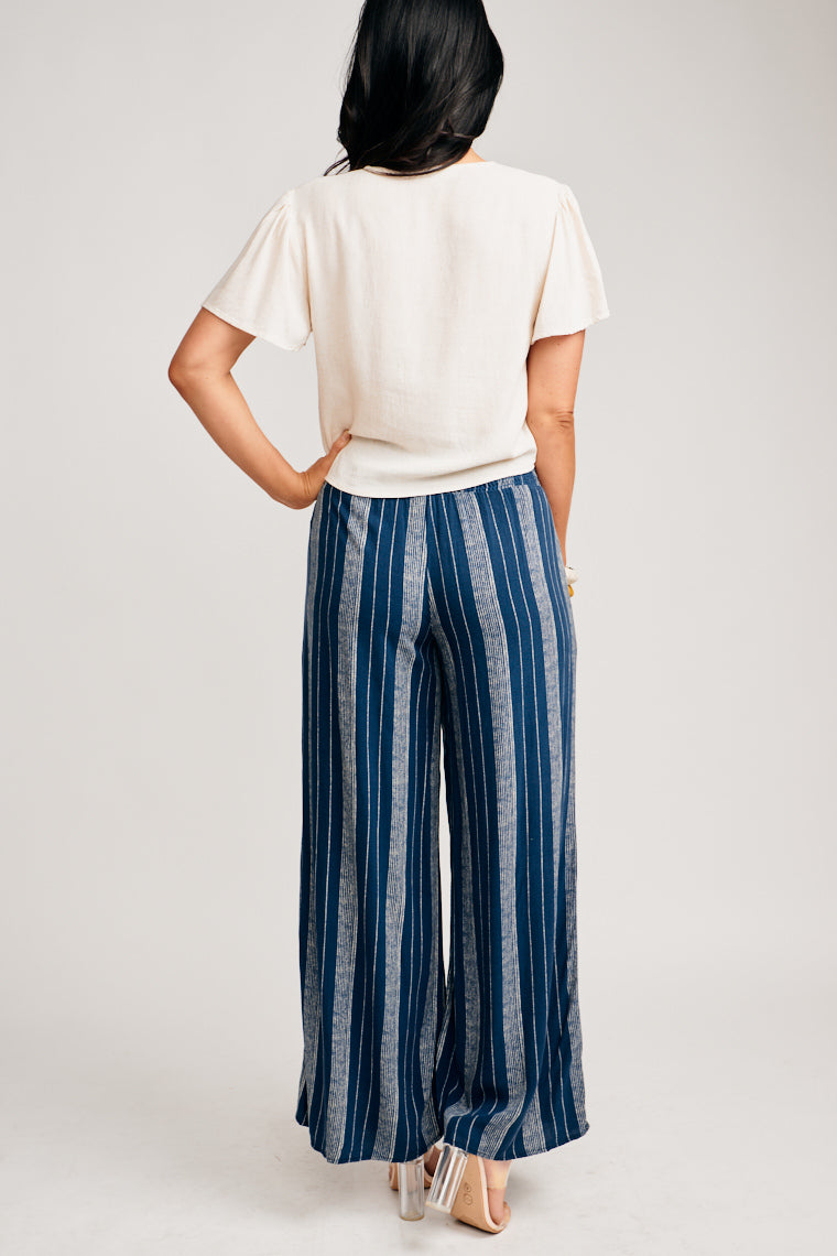 These lightweight pants have white striped prints on navy fabric. The smocked waist attaches to flowy pant legs with pockets at side. Pair with a tie-front top and sandals!