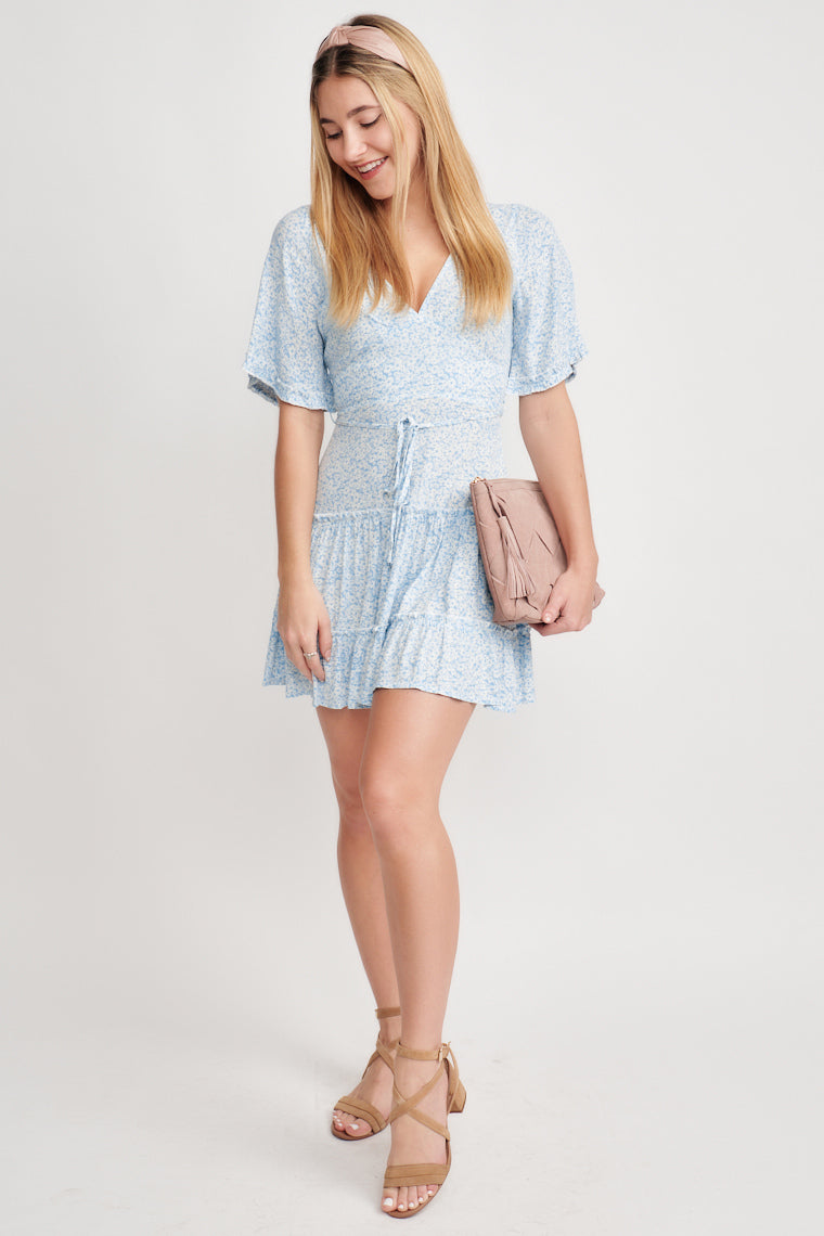 This blue and white floral printed dress offers a v-neckline that flows into a tiered ruffle skirt with a tied waistline, featuring a ribbon ruffle on the sleeve.