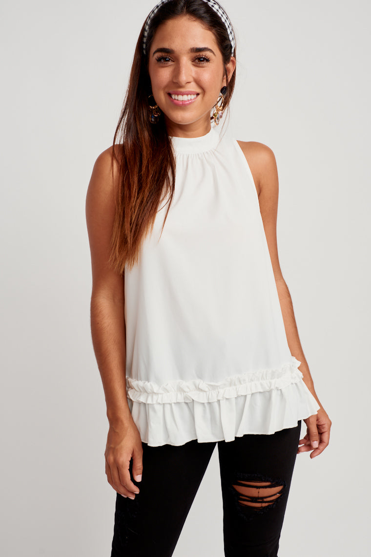 This tank has a banded halter neckline that gently ruffles and drapes down to an oversized silhouette bodice with ruffle detailing at the hem.
