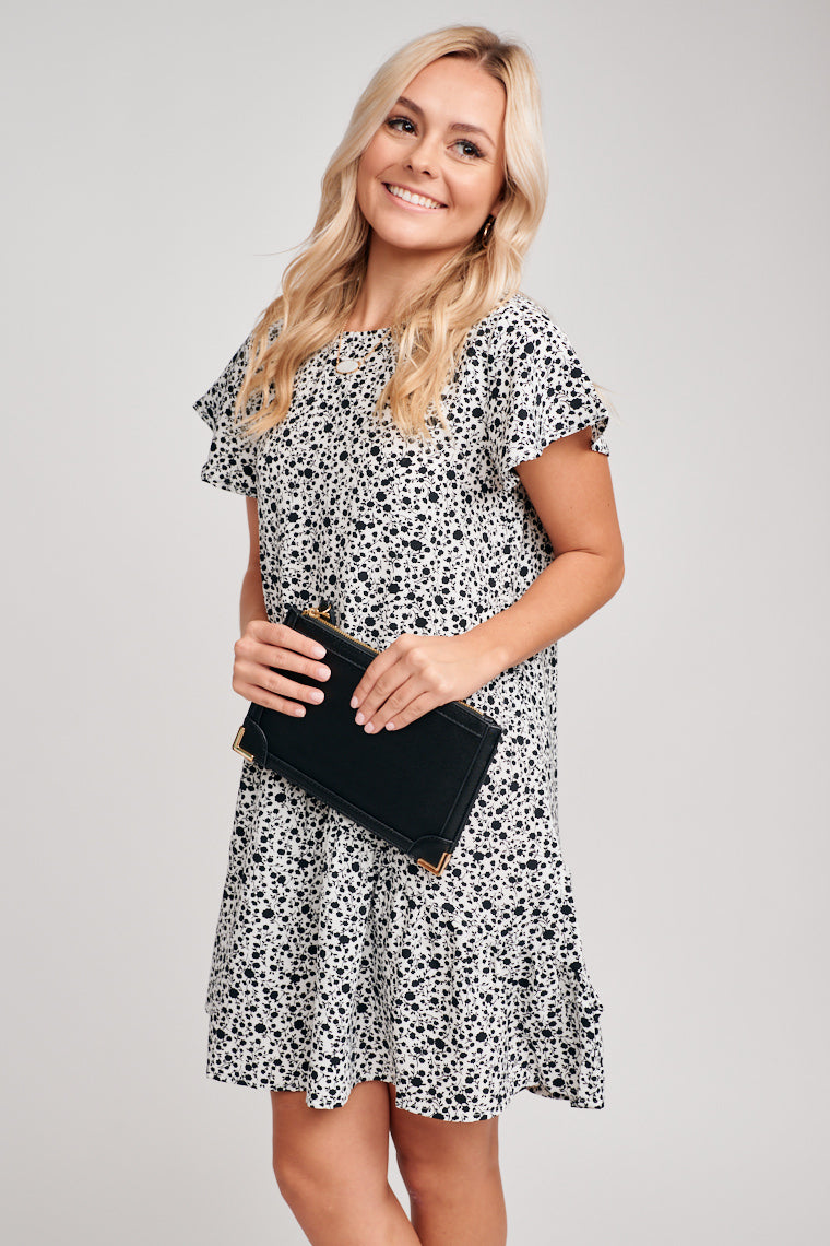 Black floral prints decorate this babydoll dress with a crew neckline and flutter sleeves. The bodice is oversized and relaxed then leads to a skirt with asymmetrical ruffle hem.