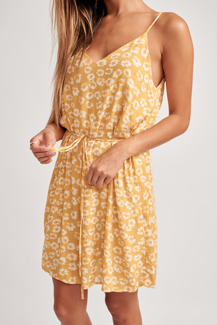 Sunshine yellow with off white florals decorates this sundress. Skinny straps, v-neckline and v-back with a tie feature to highlight your waistline.