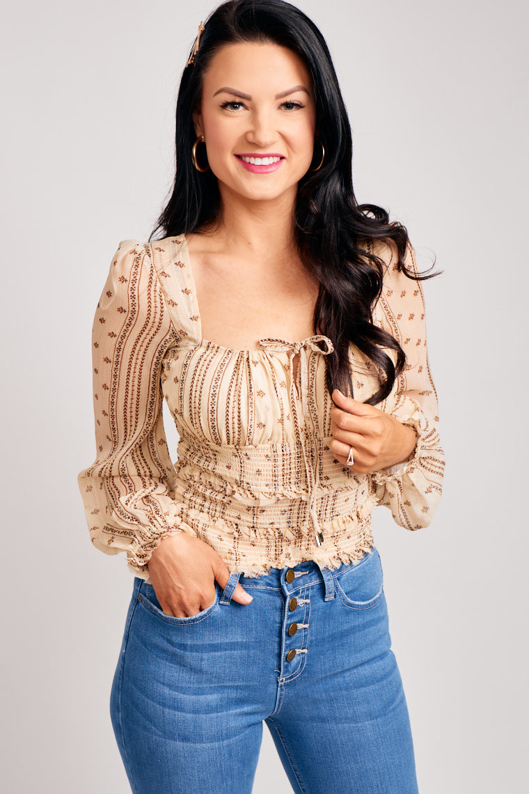 This long-sleeve elastic cuff top has a square neckline with a shirred bust panel with a drawstring fabric tie and leads to a fitted tier smocked bodice.